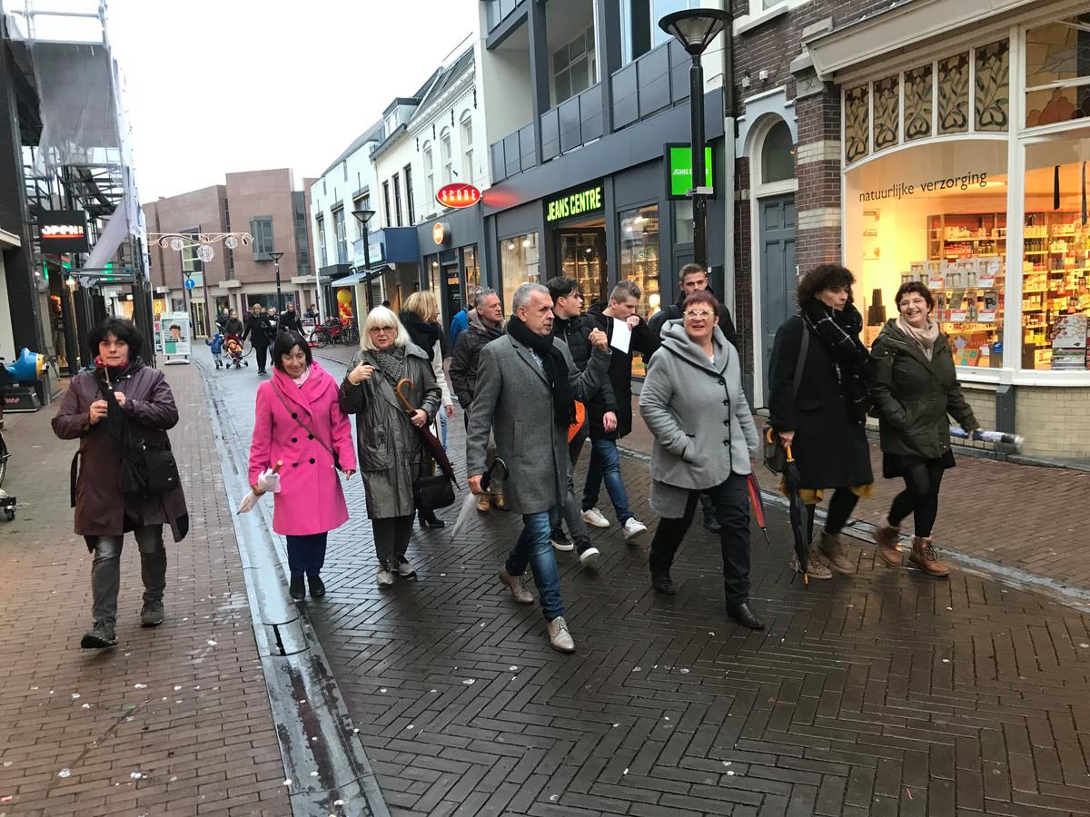 Deelnemers aan een 'creatieve wandeling' door het centrum van Oss onder leiding van centrummanager Jac van Lieshout (met zwarte das)
