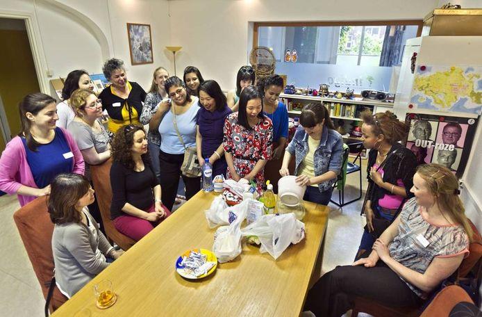 Natalia Semkiv (25) demonstreert bij Indigo World hoe je Oekraïense kwarktaart maakt. Vierde van links Carola Eijsenring (in geel-zwarte kleding). Naast haar Iro Perera. (met schoudertas). foto René Manders