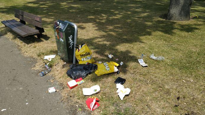Zwerfafval bij uitpuilende afvalbak in het plantsoen op de hoek van de Wilhelminasingel en de Lovensdijkstraat.