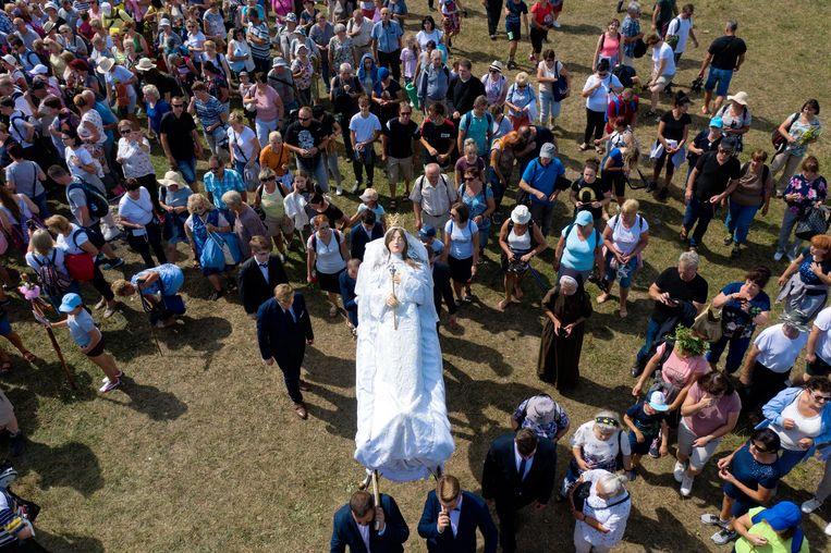 Deelnemers van een festival voor Maria-Hemelvaart in de Poolse plaats Kalwaria  Paclawska dragen een beeltenis van de Heilige Maagd. Elk jaar spelen ze haar  uitvaart na.  Beeld EPA