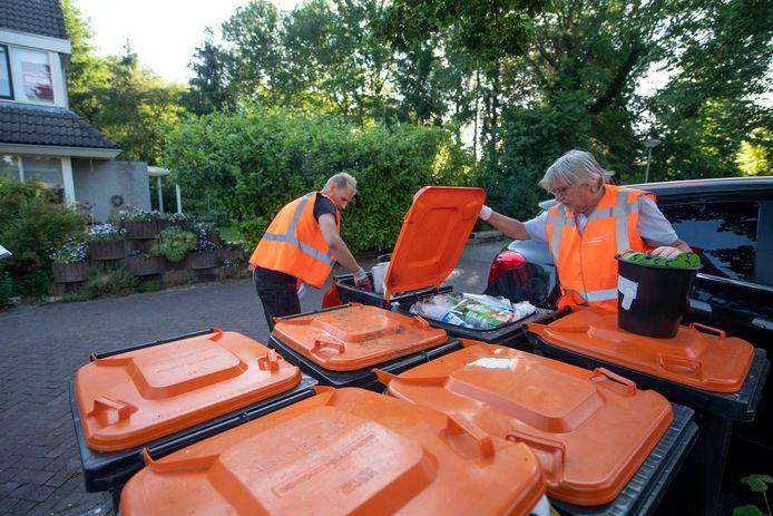 Vincent Vloedgraven (links) en milieuwethouder Henk Nijhof hielpen vorige week bij het controleren van het pmd-afval in de Kruidenwijk.