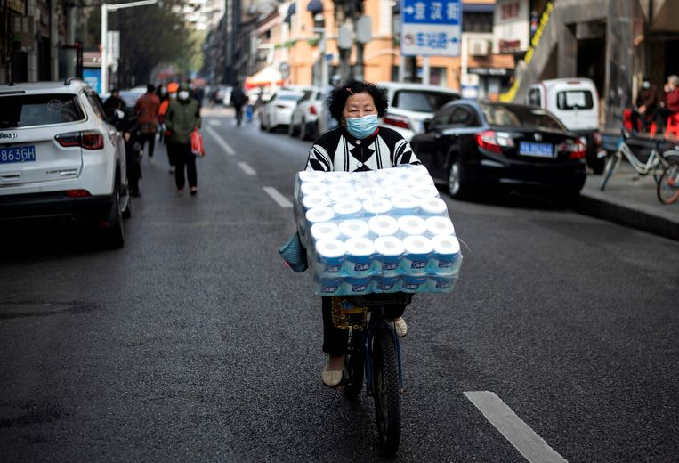 Een vrouw fietst door Wuhan met een grote lading toiletpapier. Beeld AFP