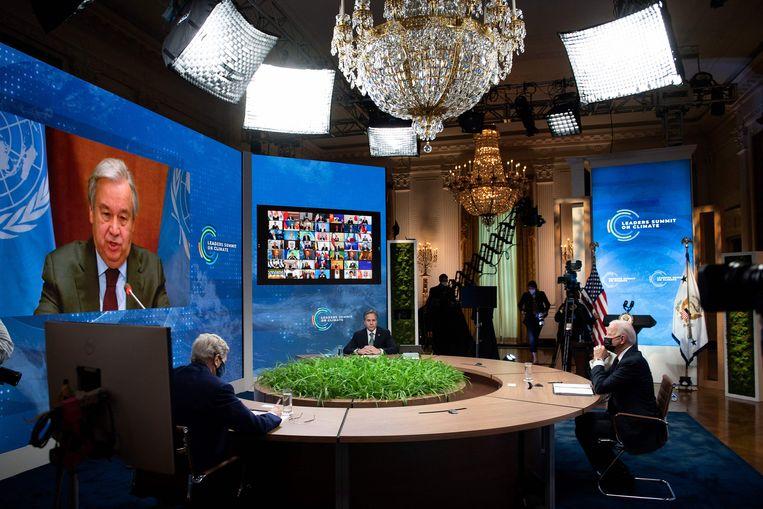 VN-secretaris-generaal Antonio Guterres (op het scherm) spreekt met onder meer VS-president Joe Biden op de virtuele klimaattop. Beeld AFP