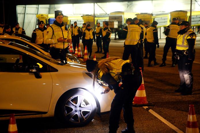 Een politie-agente controleer in het licht van een zaklamp de banden van een auto. Andere politiemensen wachten tot er nog meer auto's komen.