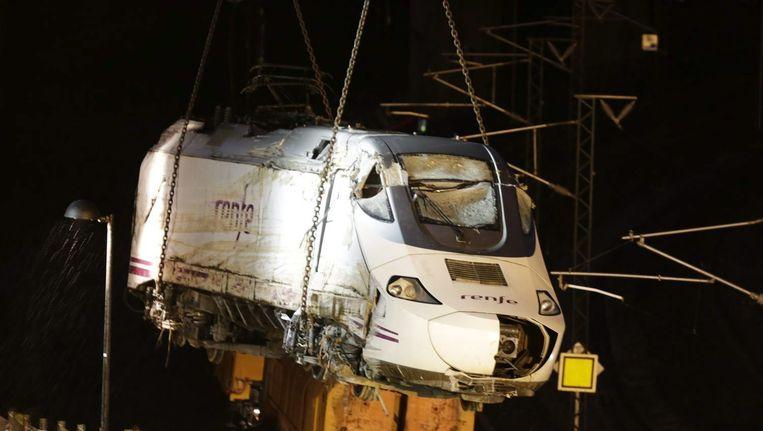 Een kraan takelt een locomotief van de ontspoorde Spaanse trein bij Santiago de Compostela weg. Werklieden waren negen uur bezig om het laatste wrakstuk te bergen. Beeld EPA