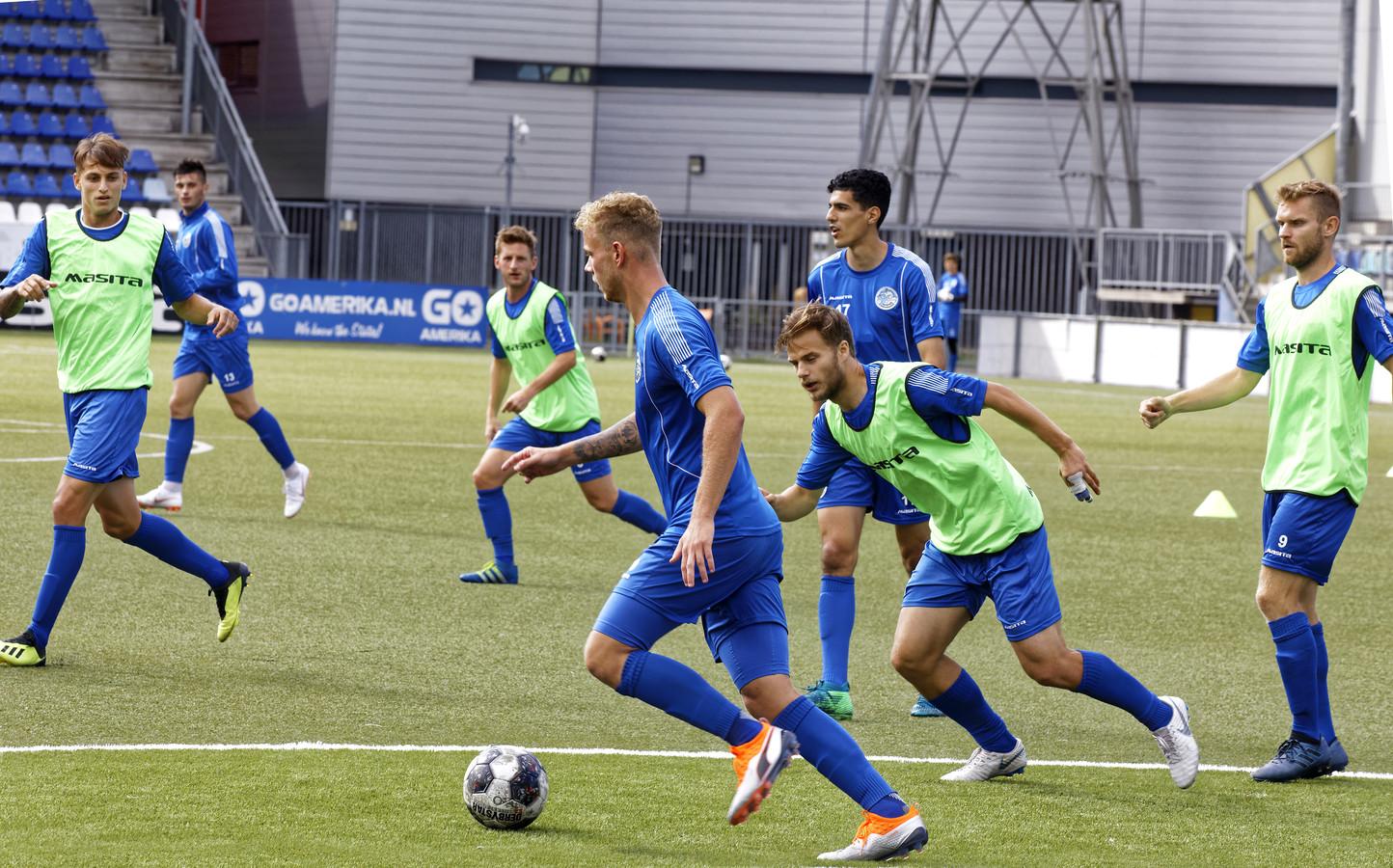Luuk Brouwers aan de bal op de training van FC Den Bosch. Van links naar rechts kijken Stefano Beltrame, Stefan Velkov, Jens van Son, Oussama Bouyaghlafen, Rauno Sappinen en Dennis Kaars toe.