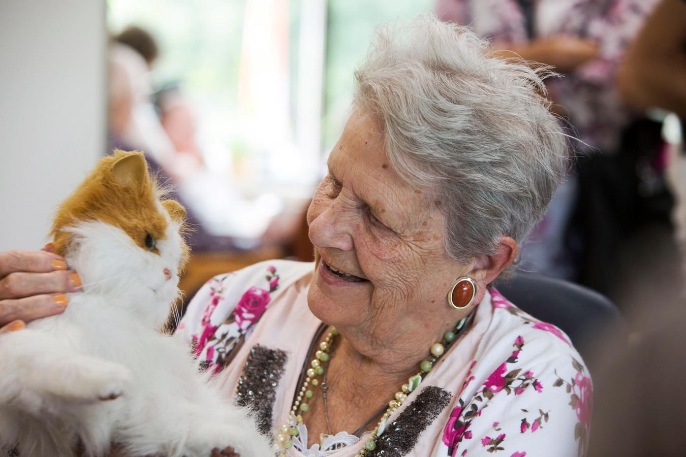 Een bewoonster van een verpleeghuis knuffelt met een robotkat. Archieffoto.
