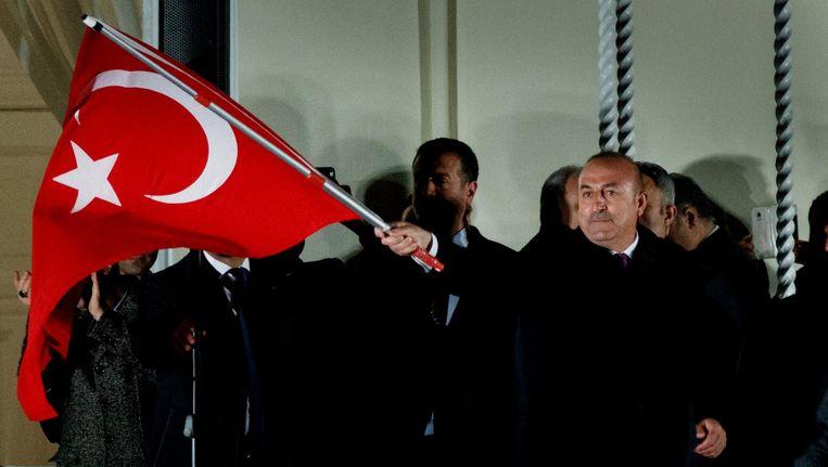 Turkse minister Cavusoglu van Buitenlandse Zaken zwaait met Turkse vlag na zijn speech voor Turkse aanhangers in Hamburg, 7 maart. Beeld epa
