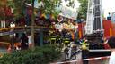 De brandweer probeert het kind onder het karretje van de attractie uit te halen. kermis tilburg