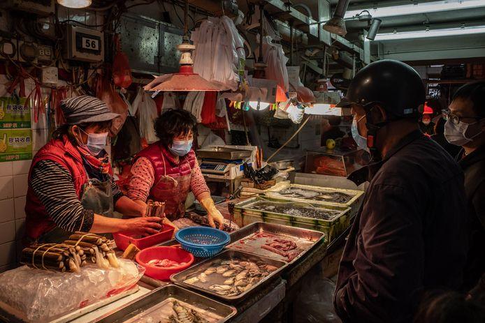 Op 'wet markets' in China dragen de verkopers nu verplicht mondmaskers.