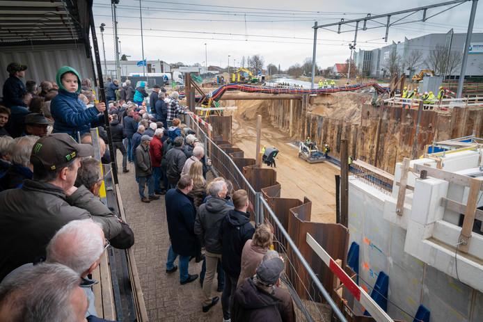 Toeschouwers op een speciale oplegger bij het plaatsen van de tunnelbak onder het spoor Dieren-Zutphen, zaterdag.