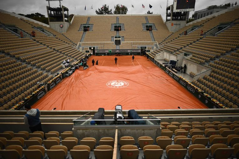 Groundstaff members pull covers across the  the Suzanne Lenglen court surface as rain falls on Day 9 of The Roland Garros 2020 French Open tennis tournament in Paris on October 5, 2020. (Photo by Martin BUREAU / AFP) Beeld AFP