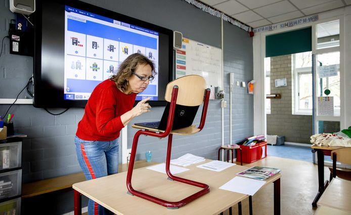 Een leerkracht neemt een video op voor kinderen van een basisschool.