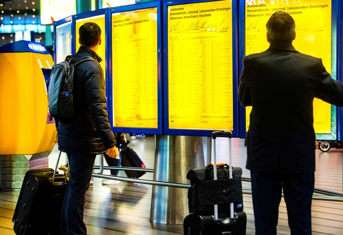 Reizigers kijken naar de borden op het station.