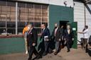 Rudy Giuliani (2e van links) betreedt met andere advocaten van president Trump het parkeerterrein van het hoveniersbedrijf waar journalisten zijn verzameld voor de persconferentie.