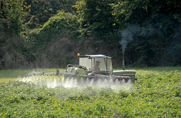 Een Belgische boer spuit pesticiden op zijn gewassen. Beeld getty