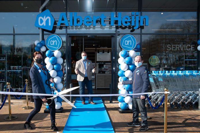 Filiaalmanager Tom Stuart en Michel Hondijk zien hoe Nicole Waas het lint doorknipt en daarmee de vernieuwde Albert Heijn in winkelcentrum Meijhorst opent.