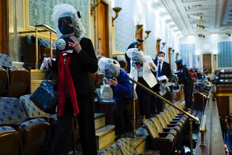 Tijdens de bestorming van het Capitool moesten politici en medewerkers in gasmaskers schuilplaatsen opzoeken. Beeld AP