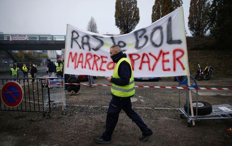 Een spandoek maakt duidelijk dat de Fransen het beu zijn om zoveel te betalen aan de pomp. Beeld REUTERS