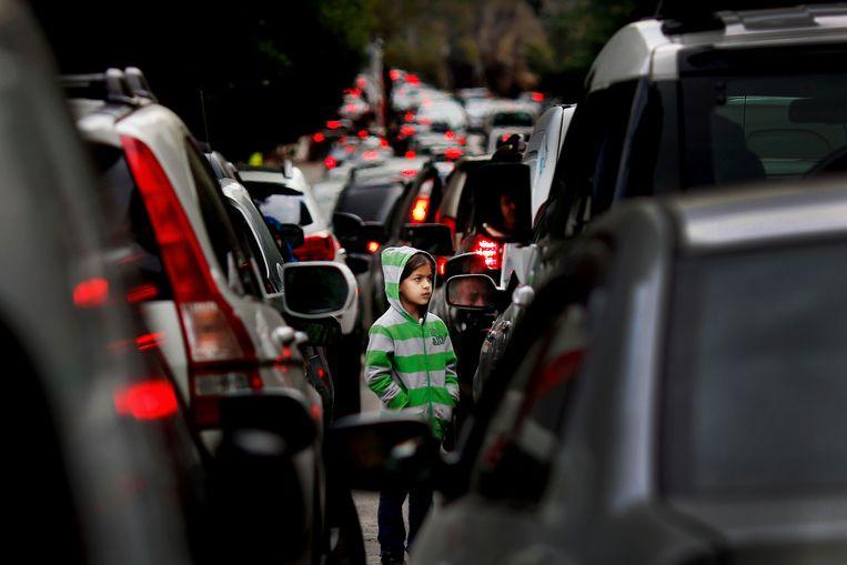 Een Syrisch jongetje loopt te bedelen bij automobilisten in een file in Beiroet. Beeld AP