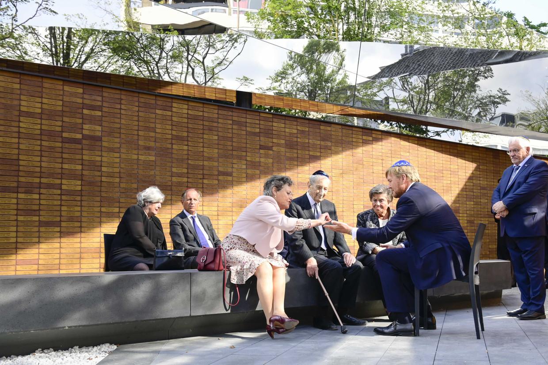 Koning Willem-Alexander praat met overlevenden van de Tweede Wereldoorlog na afloop van de onthulling van het Holocaust Namenmonument in Amsterdam. Beeld ANP