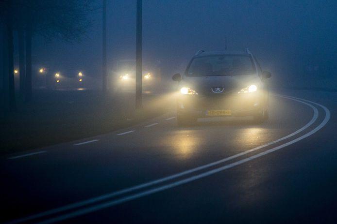Een auto rijdt door de mist. Het KNMI heeft code geel afgegeven voor plaatselijk zeer dichte mist.