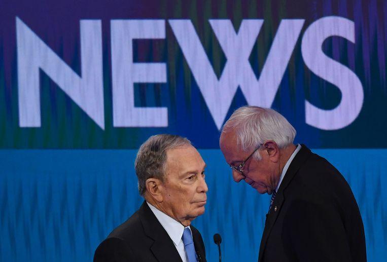 Michael Mike Bloomberg (l.) zijn concurrent Bernie Sanders tijdens het debat in Las Vegas. Beeld AFP