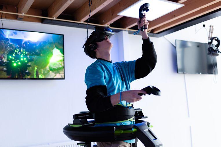 Een speler neemt bij Virtuality aan de Westerdoksdijk in Amsterdam virtuele tegenstanders onder vuur terwijl hij in de Omni staat, een virtual reality-installatie met ingebouwde loopband. Beeld Katja Poelwijk