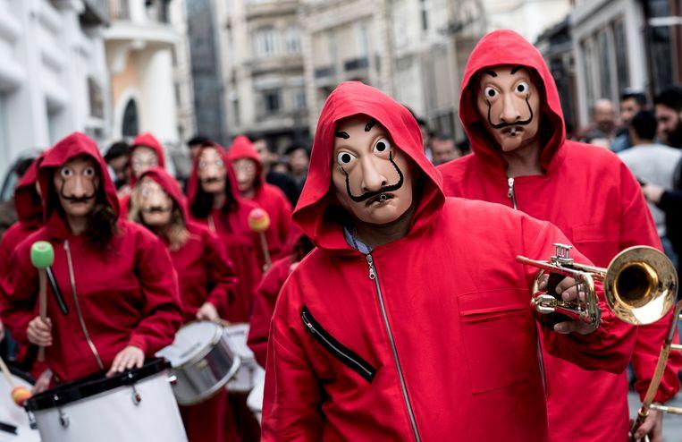 Mensen met een masker op uit de serie 'La casa de papel.' Beeld EPA