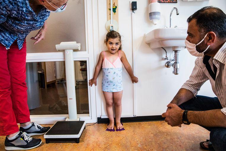De 3-jarige Malak heeft haar voeten netjes tegen de muur gedrukt. 'Haar lengte ziet er goed uit.' Vader Khalid kijkt toe. Beeld Aurélie Geurts