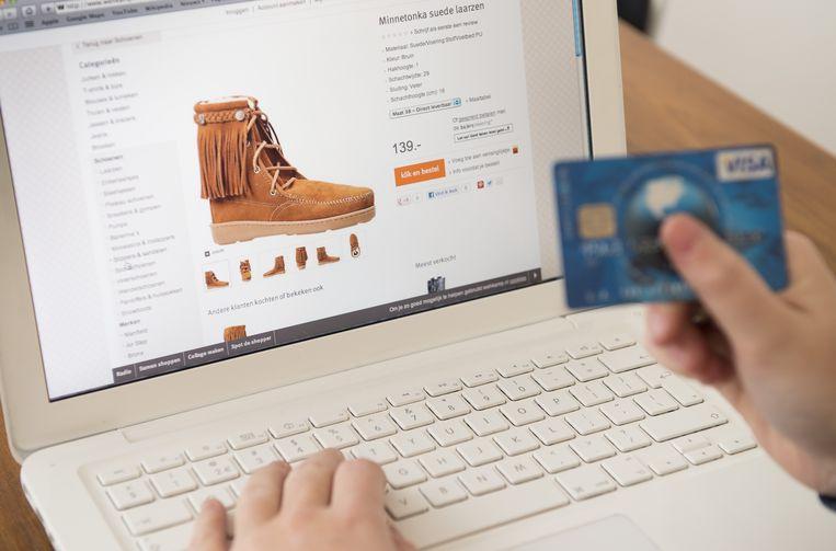 Een consument staat op het punt online een paar schoenen te kopen. Recensies spelen een belangrijke rol bij online-aankopen, zodat bedrijven veel neprecensies plaatsen. Daaraan wil het kabinet nu paal en perk stellen. Beeld ANP