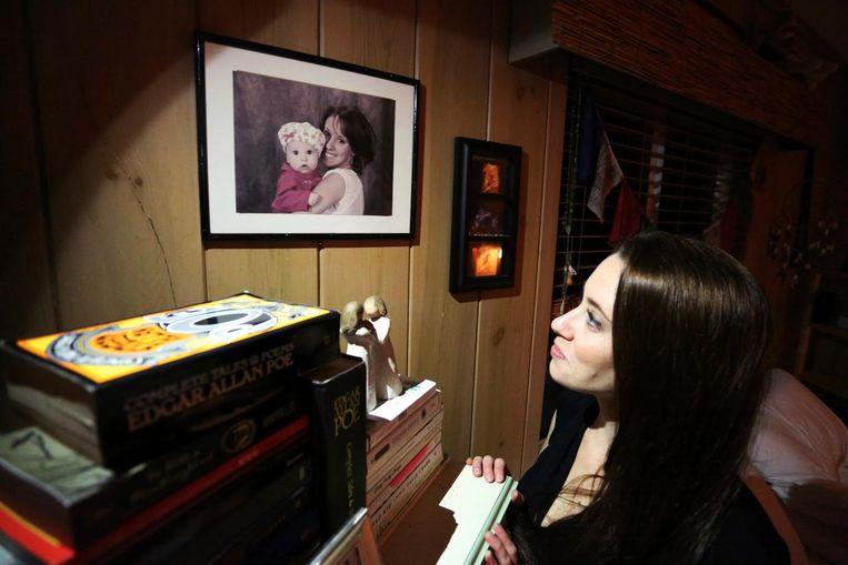 In haar slaapkamer bij een portret van haar en haar dochtertje.