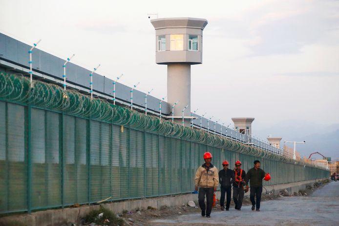 Des travailleurs passant devant la clôture de ce qui est officiellement connu comme un centre de formation professionnelle à Dabancheng, dans la région autonome ouïgoure du Xinjiang. En réalité il s'agirait d'un camp de concentration.