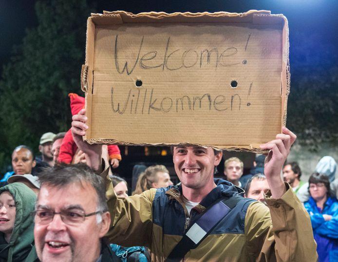 September vorig jaar: een man houdt een welkomstbord op tijdens de aankomst van vluchtelingen aan het treinstation in Saalfeld.