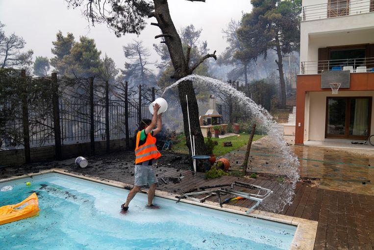 Voorzorgsmaatregelen in Ippokratios Politia, een dorp nabij Athene.  Ten noorden van de hoofdstad woedden vrijdag 95 branden. Beeld AP