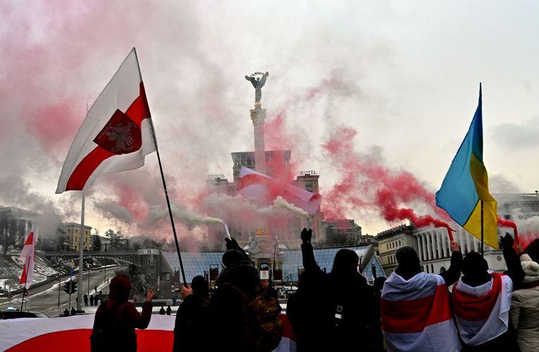 Leden van de Wit-Russische diaspora houden samen met Oekraïense activisten vlaggen in de lucht in het centrum van Kiev op de dag van de 'internationale solidariteit voor Wit-Rusland' op 7 februari 2021. Beeld AFP