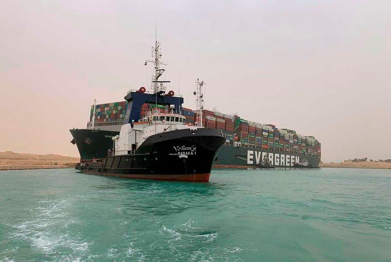 De Ever Given (met de tekst Evergreen) blokkeert de doorgang voor andere schepen. De foto is verstrekt door de autoriteiten van het Suezkanaal. Beeld AP