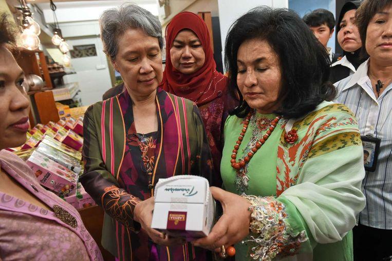 De first ladies van Maleisië (midden rechts) en Singapore (midden links) bekijken Maleisische chocolade bij de opening van de Maleisische `Agrobazaar' in Singapore, 27 augustus. Beeld null