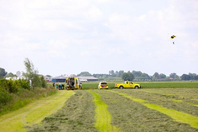 Ambulances schieten de gewonde parachutist bij Teuge te hulp. Er is ook een traumahelikopter ter plaatse.