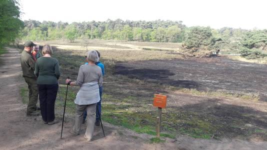 Bezoekers bekijken een dag na de brand de brandplek die is ontstaan.