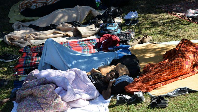 Migranten slapen nu in het park in Como. Beeld Photo News