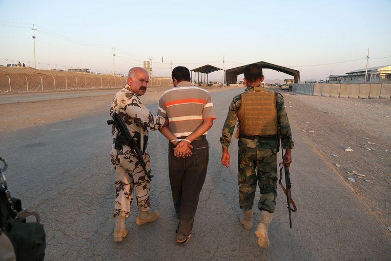 Koerdische strijders nemen een man gevangen van wie zij vermoeden dat hij voor IS vecht. Locatie: Khazer checkpoint, net buiten Erbil. Beeld ap