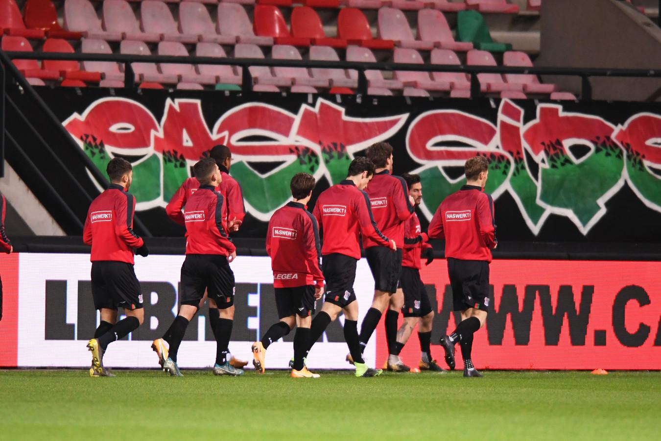 NEC-spelers warmen op in een leeg stadion.