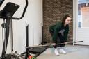 Céline Cacchione heeft in de garage een fitnesshoek ingericht waar ze met gewichten aan de slag gaat nu de sportscholen zijn gesloten.