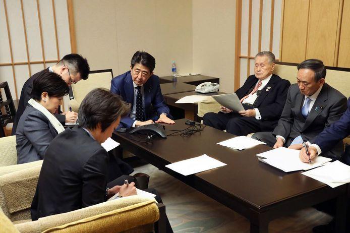 Na dit gesprek werd de beslissing genomen. Premier Shinzo Abe (centraal), Yoshiro Mori (2de van rechts), voorzitter van het organisatiecomité, en enkele ministers en kabinetsleden bellen met het IOC en voorzitter Thomas Bach (onder).