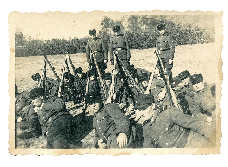 Iwan Demjanjuk is de man die op op de voorgrond in het midden ligt. Links achter de bomen, precies boven de meest linkse driehoek van geweren, is volgens de Duitse organisatie Bildungswerk Stanislaw Hantz de schoorsteen van de gaskamers te zien. Beeld United States Holocaust Museum