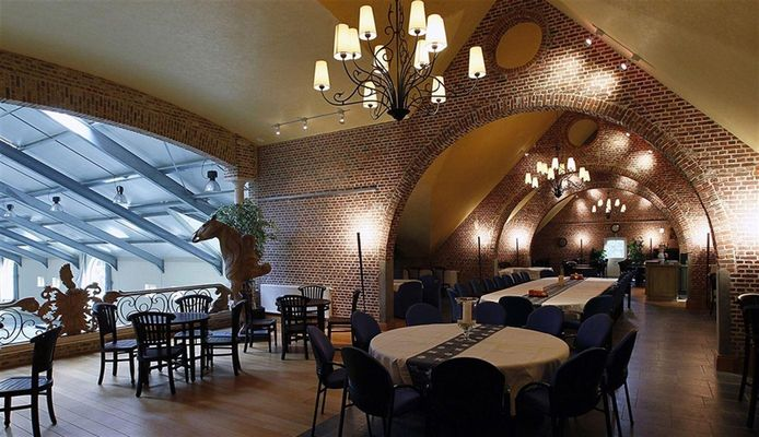 Een dineerzaal die uitkijkt op de indoor-manège.