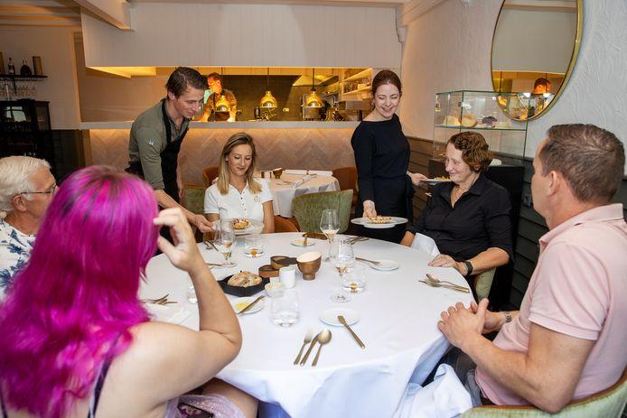 Gastvrouw Laura van der Velden en haar partner, chef-kok Chiel Sap, presenteren een van de gerechten.