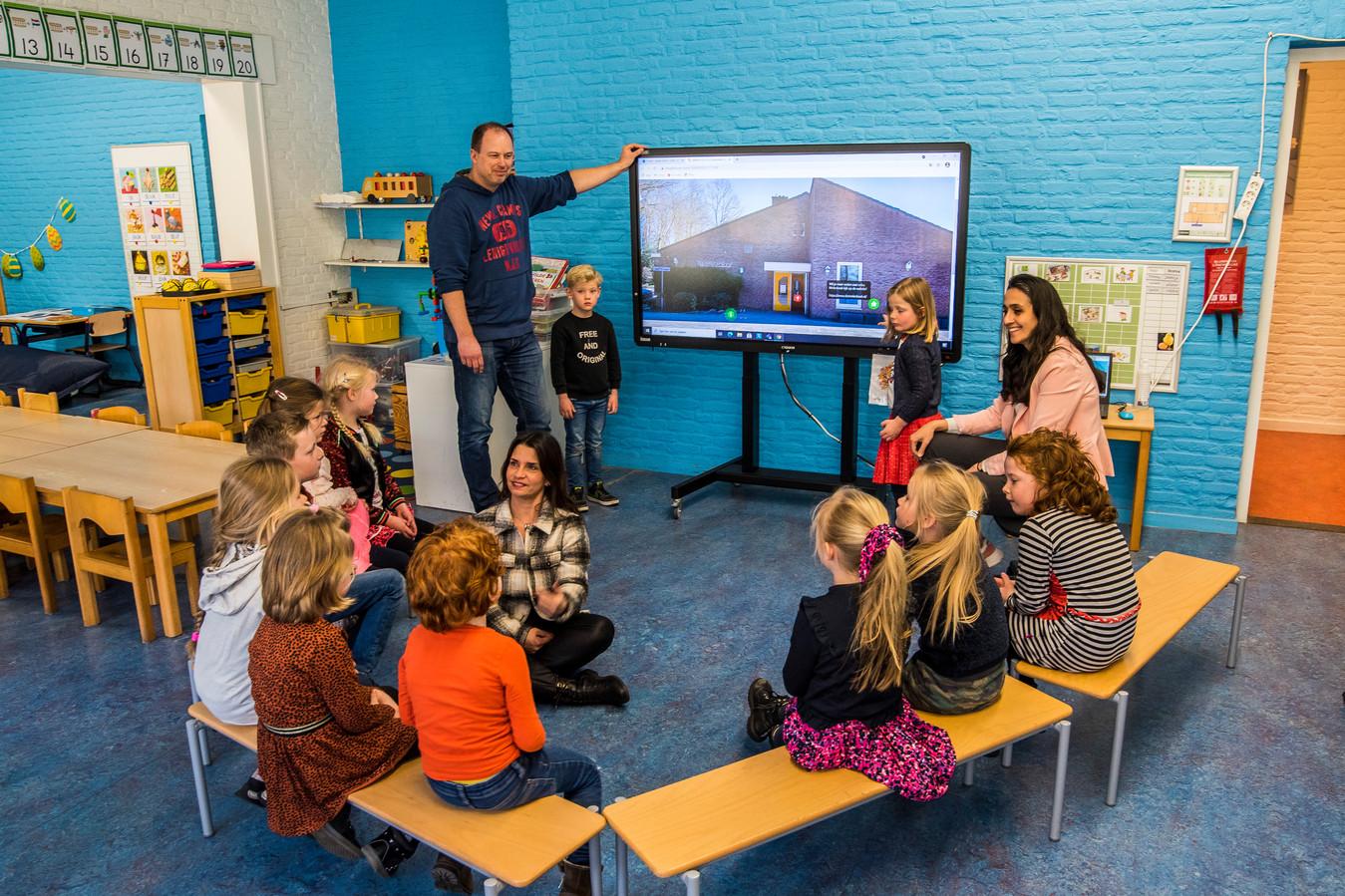 Scholieren van de openbare basisschool Molenbeek in Usselo kijken naar een virtuele schoolpresentatie gemaakt door leerlingen van Het Assink lyceum.