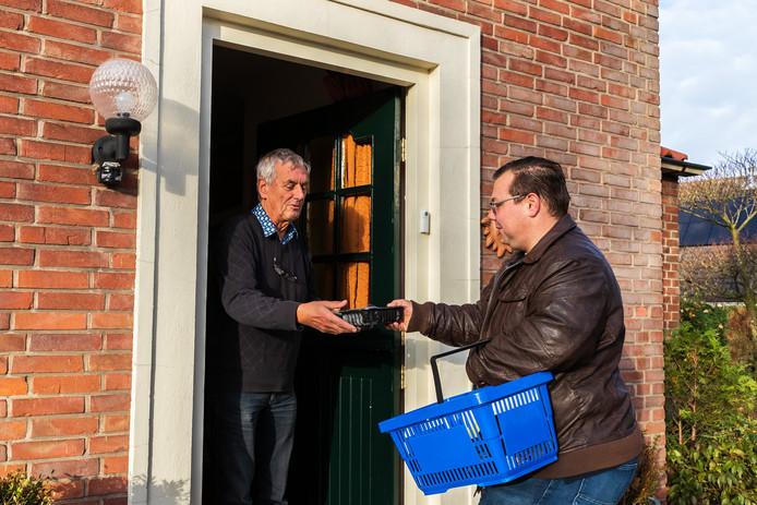 Wim Ellenkamp (links) neemt een bak soep aan van Ruud Grooters van voetbalclub Sp Haarlo.